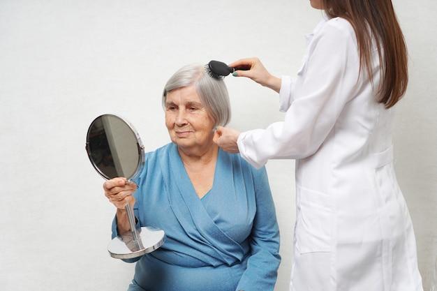 Visitante de saúde, penteando o cabelo da mulher sênior.