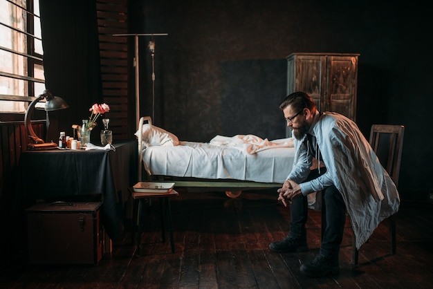 Visitante masculino contra cama de hospital vazia