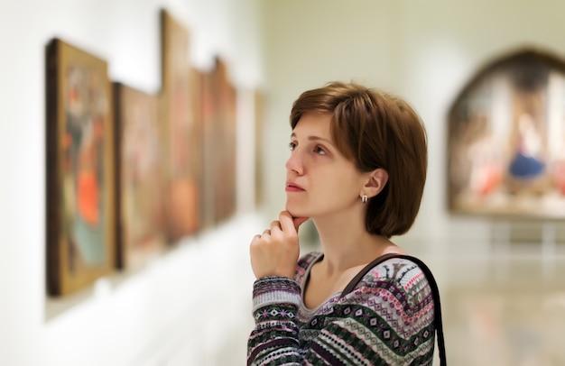 Visitante que olha imagens na galeria de arte