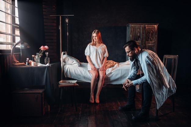 Visitante sentado contra uma mulher doente na cama do hospital