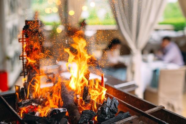 Visitantes do restaurante no de uma grelha em chamas.