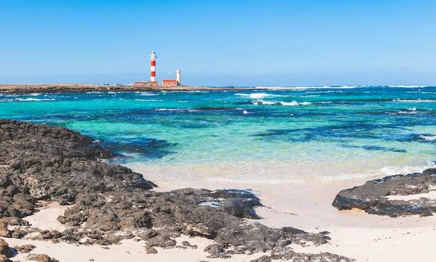 Vista à beira-mar em fuerteventura com água limpa e farol