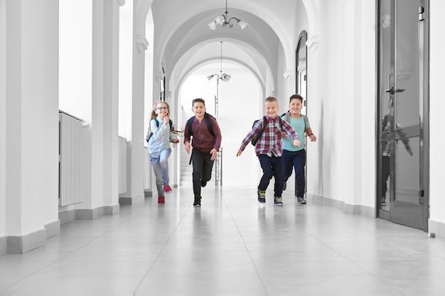 Vista à distância de três meninos e uma menina loira brincando juntos e correndo no longo corredor branco da escola.
