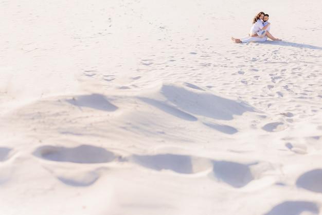 Vista à distância jovem casal sentado e se abraçando na areia, olhando para a câmera
