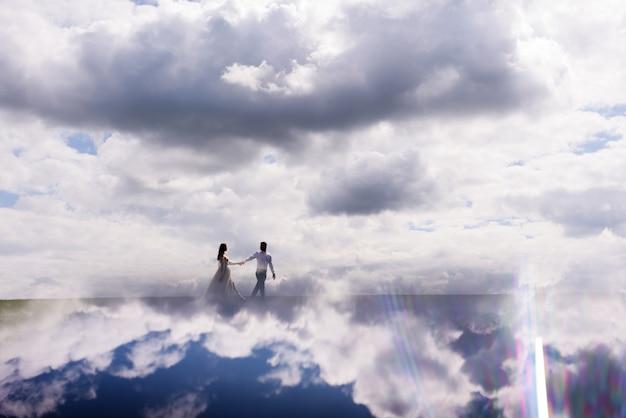 Vista à distância, recém-casados caminhando nas nuvens