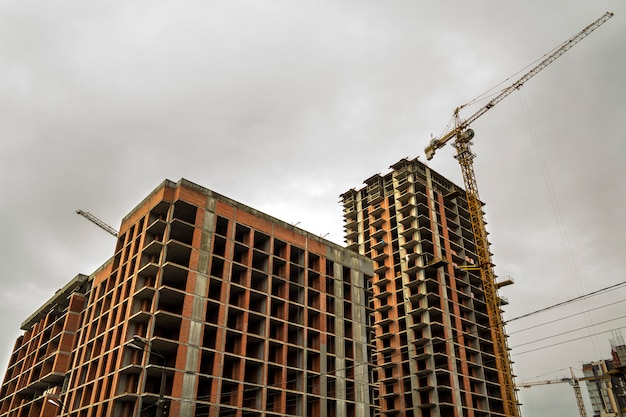 Vista à terra de um novo edifício residencial moderno em construção. conceito de desenvolvimento imobiliário. casa de vários andares de tijolos e concreto. guindaste de torre do canteiro de obras no trabalho.