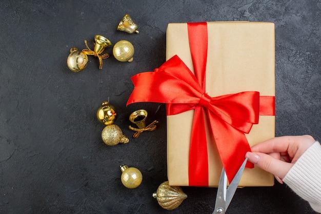 Vista acima da mão cortando a fita vermelha na caixa de presente e acessórios de decoração em fundo escuro