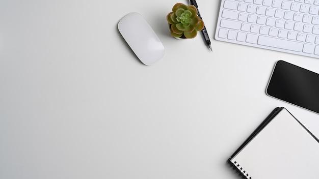 Vista acima da mesa de escritório branca com caderno vazio, telefone inteligente, teclado, cacto e espaço de cópia.