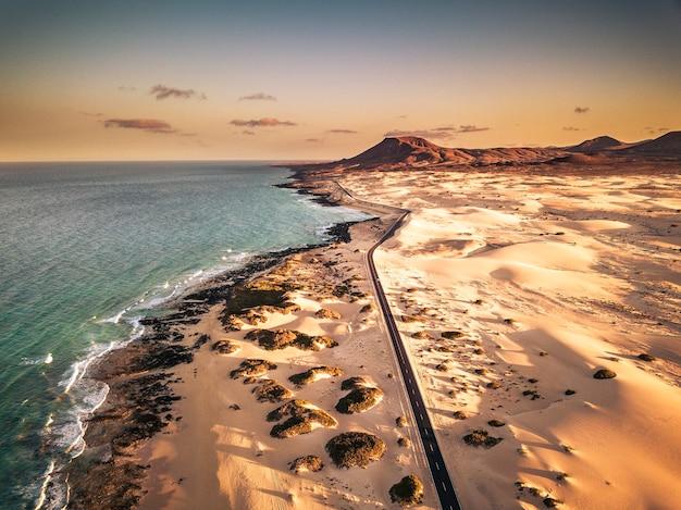 Vista aérea acima da praia de areia tropical amarela com estrada longa preta e carro viajando - ondas do oceano azul e costa - hora do pôr do sol com sombra longa bonita - conceito de férias de verão - montanha