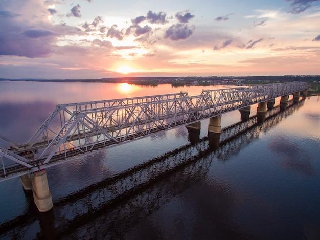 Vista aérea bonita da ponte railway através do rio volga no por do sol. ele conecta dois bancos através do rio volga