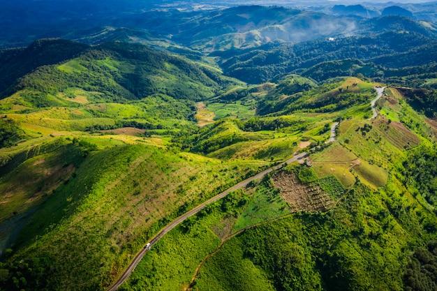 Vista aérea caminho de estrada no pico da montanha verde na estação da chuva