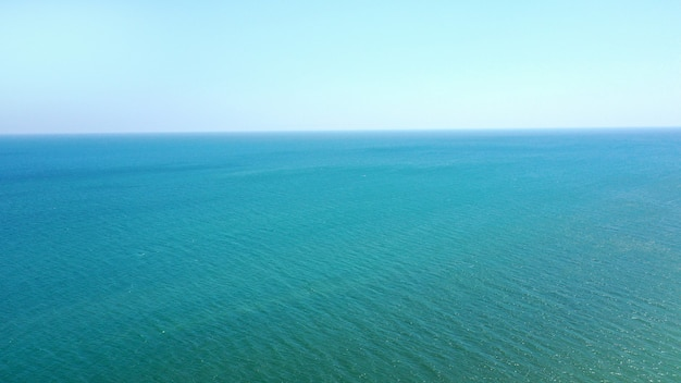 Vista aérea da água azul do mar calmo e do céu sem nuvens. lugar para texto.