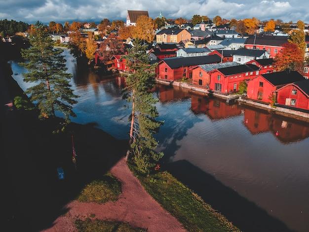 Vista aérea da antiga casa vermelha e celeiros à beira do rio