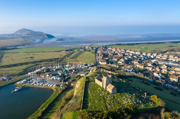Vista aérea da antiga igreja de são nicolau em uphill e do estaleiro perto de weston super mare, reino unido