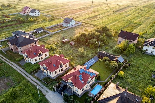Vista aérea da área residencial rural com casas particulares entre campos verdes ao nascer do sol.