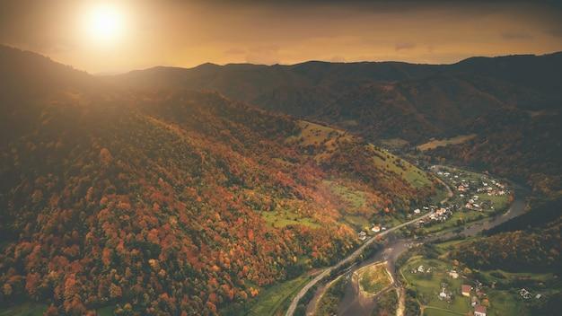 Vista aérea da bela vila do desfiladeiro localizada ao longo do rio, dramática paisagem montanhosa de outono com