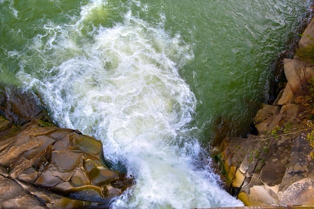 Vista aérea da cachoeira do rio com águas turquesas claras caindo entre pedregulhos molhados com espuma branca espessa. Foto Premium