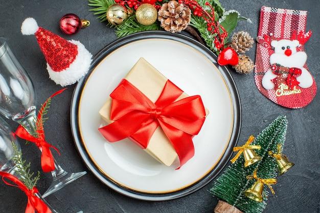 Vista aérea da caixa de presente no prato de jantar árvore de natal ramos de coníferas cone de papai noel chapéu caídas taças de vidro em fundo preto