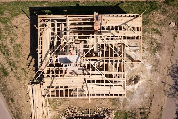 Vista aérea da casa de tijolo inacabado com estrutura de telhado de madeira