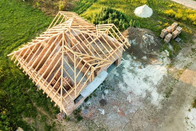 Vista aérea da casa de tijolos inacabada com estrutura de telhado de madeira em construção.