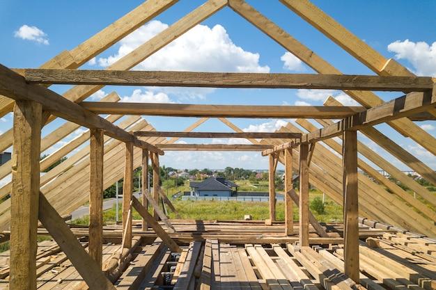 Vista aérea da casa inacabada com estrutura de estrutura de telhado de madeira em construção.