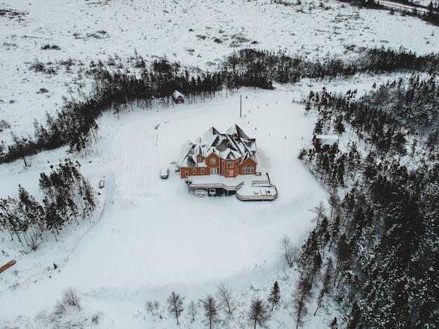 Vista aérea da casa marrom no campo de neve