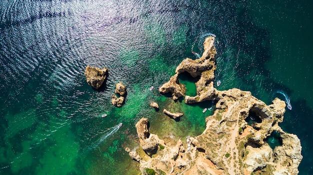 Vista aérea da cênica ponta da piedade de lagos, portugal. falésias íngremes à beira-mar e águas do oceano azul na região do algarve em portugal