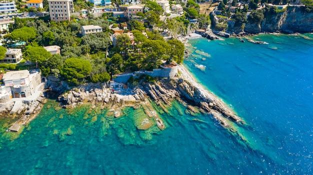 Vista aérea da cidade com as casas coloridas localizadas na costa rochosa do mar da ligúria, camogli perto de gênova, itália. rocky coastline é lavado com água azul turquesa.