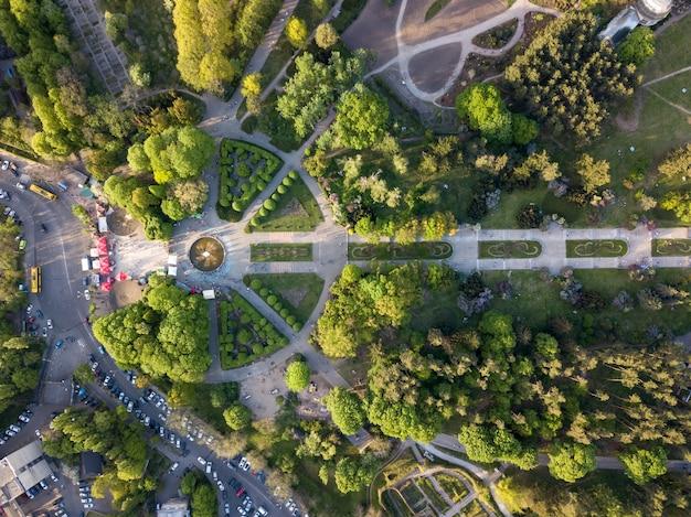 Vista aérea da cidade de kiev é um jardim botânico com becos e pessoas em uma caminhada e uma estrada com carros estacionados.