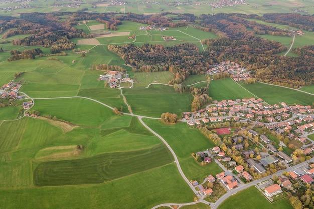 Vista aérea da cidade pequena, com telhados vermelhos entre campos agrícolas verdes e florestas distantes no verão.