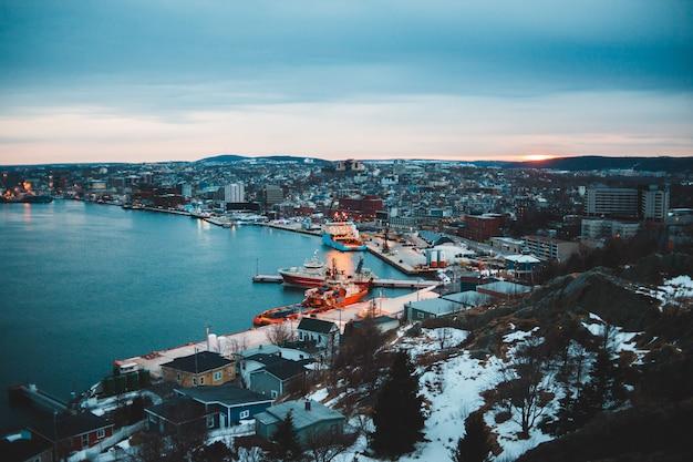 Vista aérea da cidade perto do corpo de água durante o pôr do sol