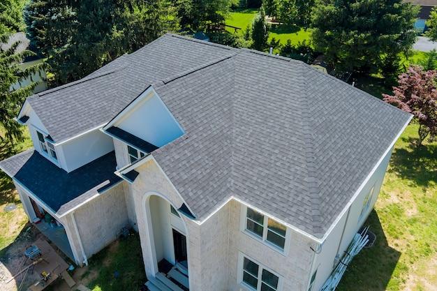 Vista aérea da construção da cobertura de telhas de asfalto, a casa com uma nova janela