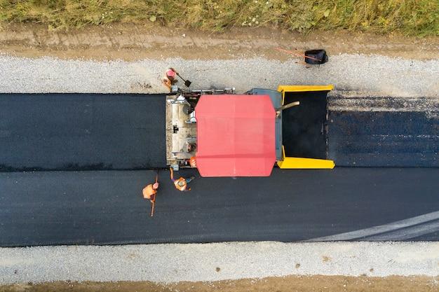 Vista aérea da construção de novas estradas com asfalto, colocando máquinas no trabalho.