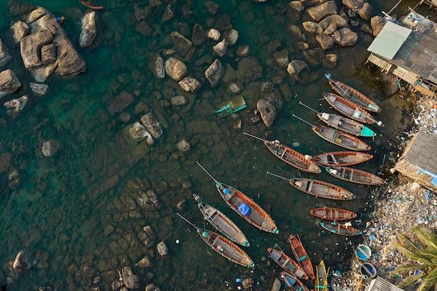 Vista aérea da costa de uma ilha com vários barcos e muitos plásticos