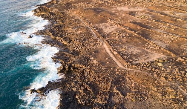 Vista aérea da costa e espuma das ondas do mar, terreno seco e trilhas, ilhas canárias