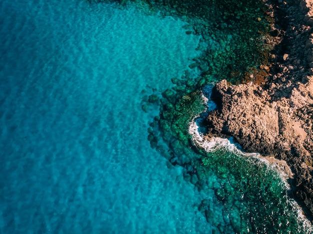 Vista aérea da costa rochosa com águas azuis cristalinas perto de cape cavo greco, chipre