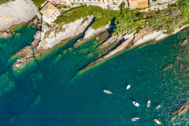 Vista aérea da costa rochosa de camogli. barcos e iates atracados perto do porto com água verde.