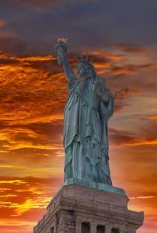 Vista aérea da estátua da liberdade ao pôr do sol na cidade de nova york, eua.