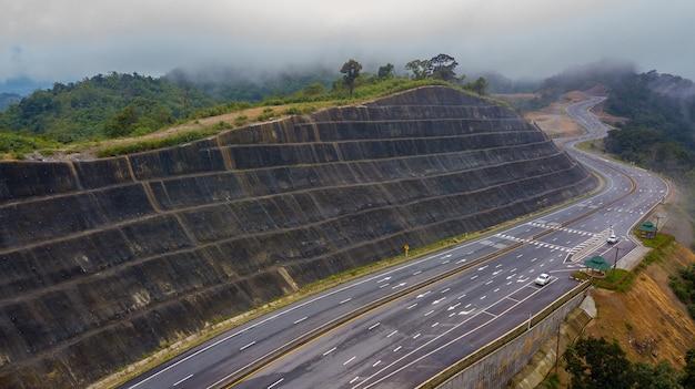 Vista aérea da estrada cênica no pico da montanha da floresta tropical em meio a nuvens ou neblina.