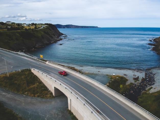 Vista aérea da estrada com veículo vermelho viajando na estrada