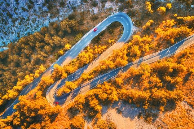 Vista aérea da estrada de montanha curva com carros, floresta laranja ao pôr do sol no outono na europa