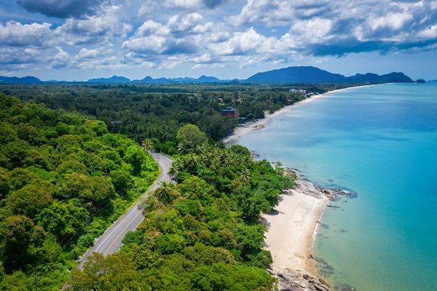 Vista aérea da estrada entre a palmeira de coco e o grande oceano durante o dia em nakhon si thammarat, tailândia