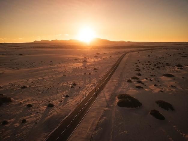 Vista aérea da estrada reta de asfalto preto no meio do deserto e montanhas - conceito de viagem em um belo lugar cênico e férias com o pôr do sol