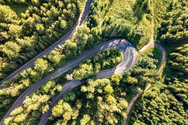 Vista aérea da estrada sinuosa em alta montanha passar através de densos pinhais verdes