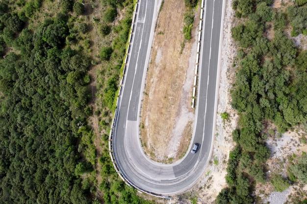 Vista aérea da estrada sinuosa em bosques de pinheiros verdes de calha de passagem de montanha alta.