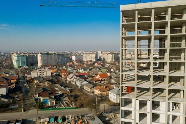 Vista aérea da estrutura de concreto de um prédio alto em construção em uma cidade.