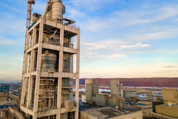Vista aérea da fábrica de cimento com alta estrutura de fábrica e guindaste de torre na área de produção industrial ao pôr do sol.