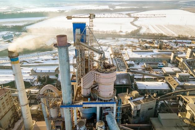 Vista aérea da fábrica de cimento com alta estrutura fabril e guindaste de torre na área de produção industrial.