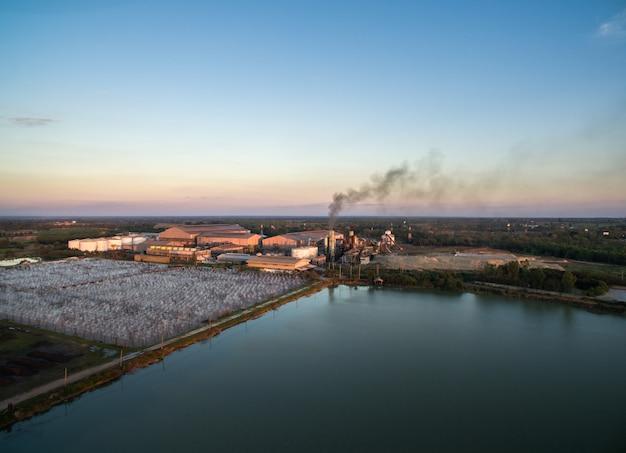 Vista aérea da fábrica do açúcar do zangão com tratamento de águas residuais no por do sol.