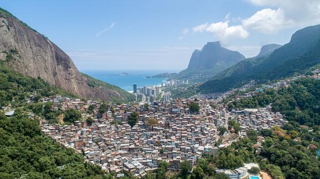 Vista aérea da favela da rocinha, a maior favela do brasil nas montanhas do rio de janeiro e o horizonte da cidade por trás